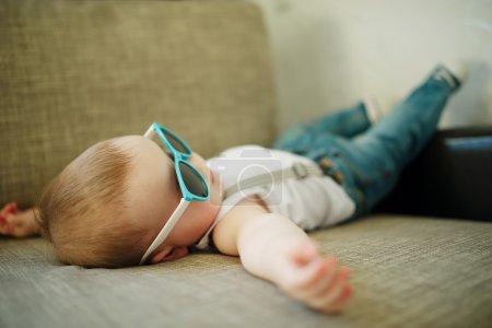 Photo pour Mignon petit garçon à lunettes de soleil à la maison - image libre de droit