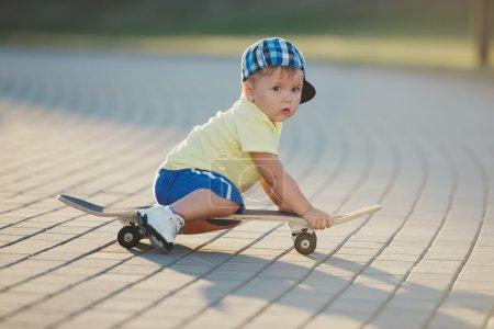 Photo pour Photo de mignon petit garçon avec planche à roulettes en plein air - image libre de droit