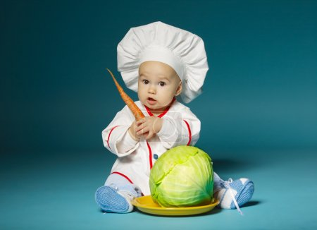 funny baby with cook costume holds carrot