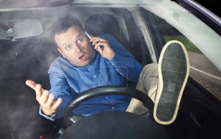 Photo pour Conducteur lors de la conversation sur téléphone portable ne se soucie pas tellement de la route qu'il a lever le pied - image libre de droit