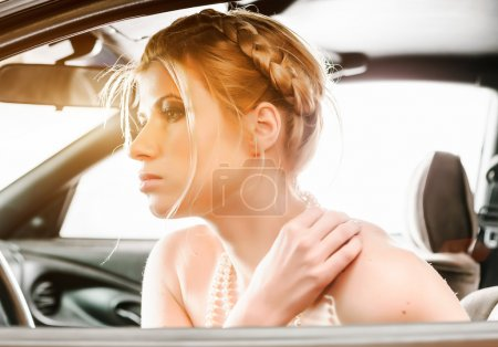 Young Woman in a pearl necklace sat In the drivers seat of her c