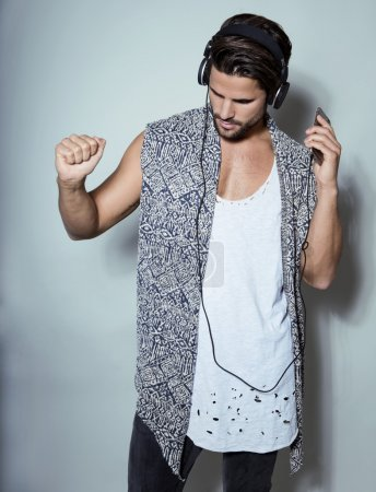 Handsome young fit man in sleeveless shirt listening to music