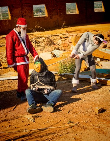 Photo for Halloween monster being taken prisoner by Santa and the Easter bunny - Royalty Free Image