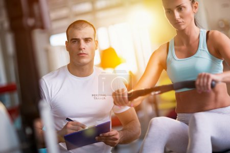 woman and trainer working out on exercise machine in gym