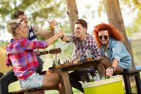 Cheerful friends toast with cold beer in forest