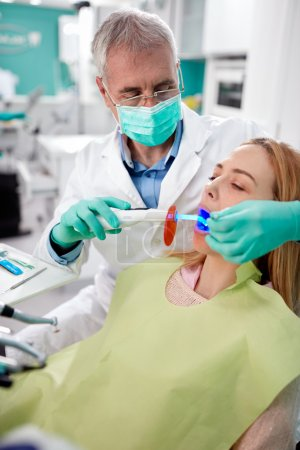 Male dentist fixed and dry dental fillings with light
