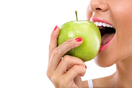 Foto de Mujer mordiendo una manzana verde aislada en blanco - Imagen libre de derechos