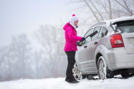 Photo pour Femme enlevant la neige de la voiture - image libre de droit