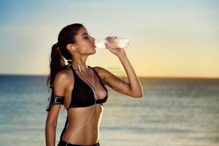 Photo pour Fitness belle femme buvant de l'eau et transpirant après l'exercice sur une journée chaude d'été à la plage. Athlète féminine après l'entraînement - image libre de droit