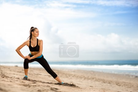 Photo for Sportswoman doing exercises on beach - Royalty Free Image
