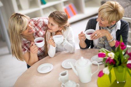 Photo pour Maman et descendant sur une visite à avec sa grand-mère, trois générations ensemble buvant le thé - image libre de droit