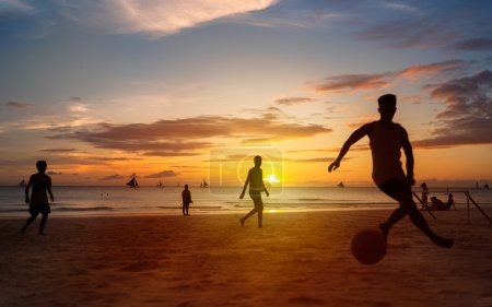 Sunset silhouettes playing beach football