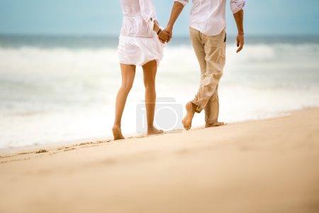 Barefoot couple walking on beach