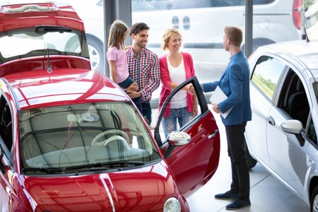 Car agent showing vehicle to young family