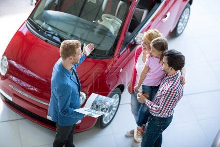 Photo for Young family in  the car dealership  saloon - Royalty Free Image