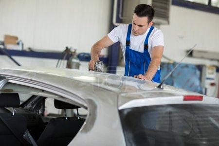Car painter fixing damage