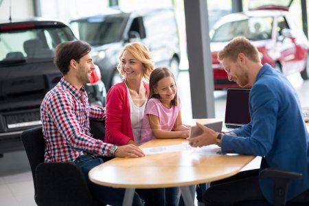 Photo for Car salesperson demonstrating new car to family - Royalty Free Image