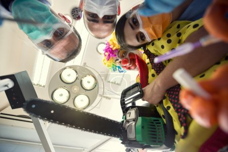 Scary clown from horror with dental team in bottom view
