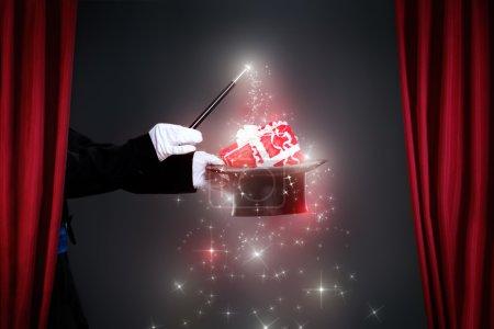 Photo pour Main de magicien avec baguette magique faisant cadeau de Noël - image libre de droit