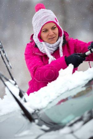 Photo pour Fille nettoyage voiture vitres de la neige - image libre de droit