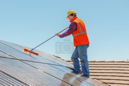 Foto de Trabajador joven limpiando paneles solares en el tejado.Enfoque en el trabajador . - Imagen libre de derechos