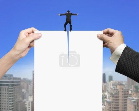 Photo pour Les mains de l'homme et de la femme tenant le livre blanc du contrat déchirant avec un homme d'affaires debout dessus, sur fond de ciel bleu et de bâtiments de la ville . - image libre de droit