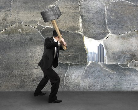 Man cracking old concrete wall
