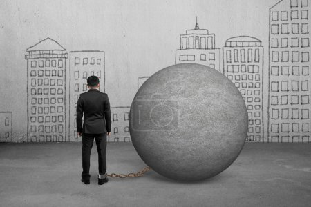 Photo pour Homme d'affaires pris au piège avec boule de béton et mur de gribouillages - image libre de droit