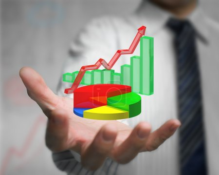 Photo pour Main d'homme d'affaires tenant infographies 3d se chevauchent, y compris graphique à secteurs colorés, graphique à barres vertes, ligne de tendance rouge - image libre de droit