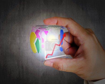 Hand hält glühend buntes transparentes Glas kubisch