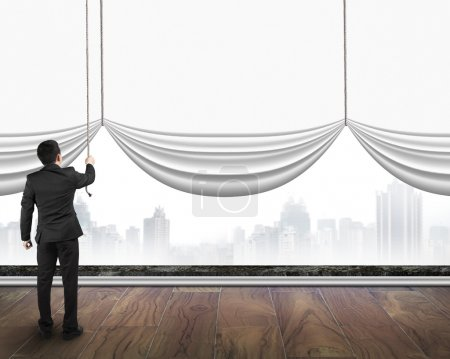 businessman pulling open blank white curtain covered gray citysc