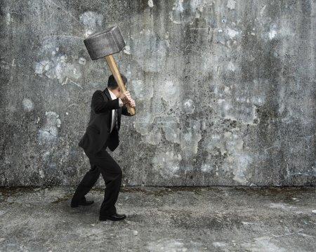 Photo pour Homme d'affaires tenir le marteau de forgeron pour casser le vieux fond de mur en béton marbré - image libre de droit