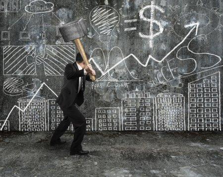 Photo pour Homme d'affaires tenir le marteau de forgeron pour casser le fond de mur en béton de gribouillis dessinés à la main - image libre de droit