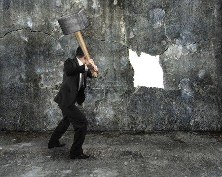 Photo pour Homme d'affaires détiennent sledgehammer fissuration grand trou de blanc sur fond de mur en béton - image libre de droit