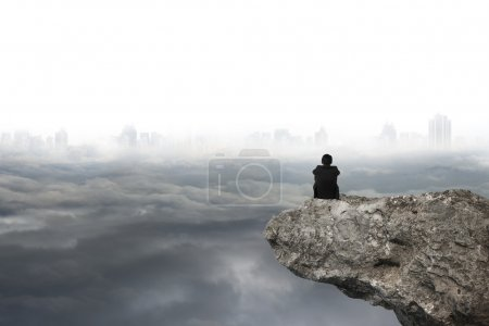 man sitting on cliff with gray cloudy sky cityscape background