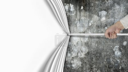 hand pulling blank curtain covered old dirty mottled concrete wa