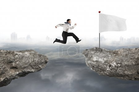 Man jumping on cliff with white flag and cloudy cityscape