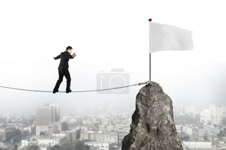 Businessman walking on rope toward white flag with cityscape