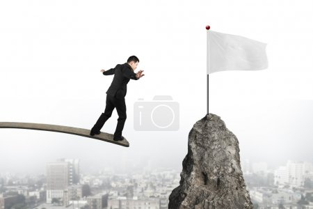 Businessman balancing on wooden board with blank white flag