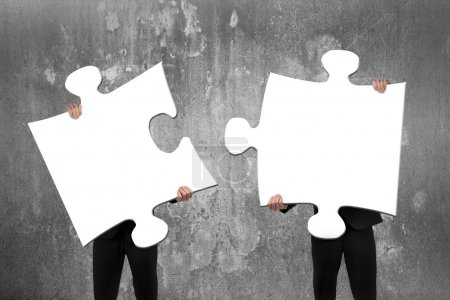 Photo for Two business people assembling blank white jigsaw puzzles with concrete wall background - Royalty Free Image
