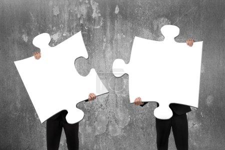 Foto de Dos empresarios que ensamblan rompecabezas blancos en blanco con fondo de pared de hormigón - Imagen libre de derechos