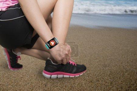Photo pour Femme sportive attachant à la main des lacets portant une montre intelligente à écran tactile avec icône d'application de capteur de santé sur fond de plage de mer naturelle - image libre de droit