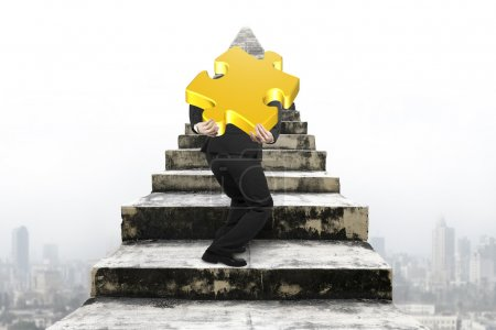 Photo pour Businessman carrying big gold jigsaw puzzle piece and climbing on old dirty concrete stairs with urban scene background - image libre de droit
