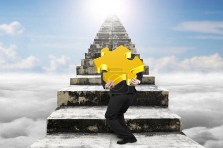 Photo pour Businessman carrying big gold jigsaw puzzle piece and climbing on old dirty concrete stairs with sky cloudscape sunlight background - image libre de droit