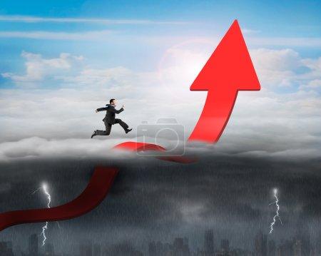 Photo pour Homme d'affaires courant sur la flèche rouge vers le haut courbant la ligne de tendance dans le ciel avec des conditions météorologiques opposées arrière-plan, ciel ensoleillé paysage nuageux, ciel couvert sombre paysage urbain pluvieux - image libre de droit