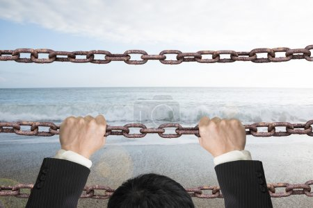 Businessman climbing on iron chains with natural sky sea