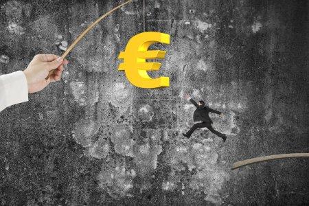 Man jumping golden euro symbol fishing lure mottled concrete wal