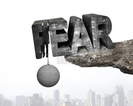 Photo for Man shackled by heavy concrete ball hanging on big 3D fear mottled word at the edge of cliff with urban scene background - Royalty Free Image