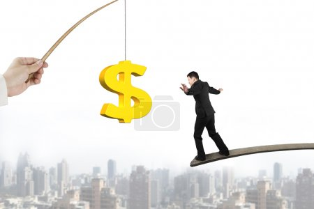 Man balancing golden dollar sign fishing lure with cityscape