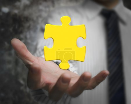 Photo pour Business man hand showing one 3D gold jigsaw puzzle piece - image libre de droit